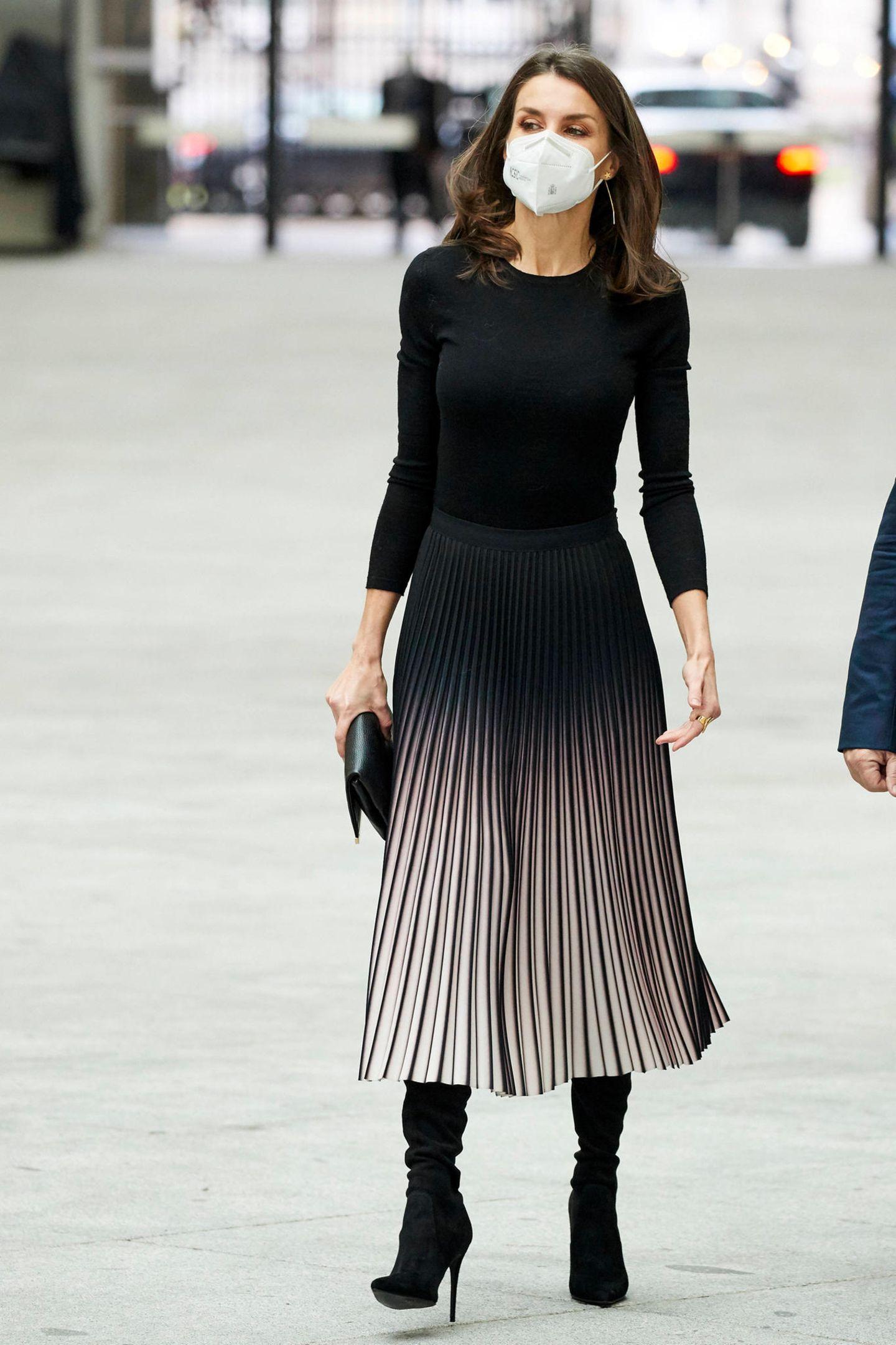 Königin Letizia ist ein echter Fashion-Profi und weiß, wie sie einen schlichten Look zum Hingucker macht. Für die Verleihung der Journalismuspreise APMin Madrid greift die spanische Monarchin zu einem schlichten Basic-Shirt und kombiniert dieses mit einem tollem Plisseerock mit Farbverlauf (von Reiss). Besonderer Hingucker:Die schwarzen Overkneestiefel von Steve Madden.
