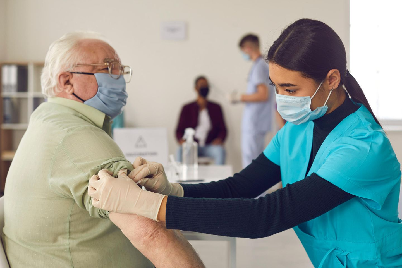 Corona aktuell: Älterer Mann wird geimpft