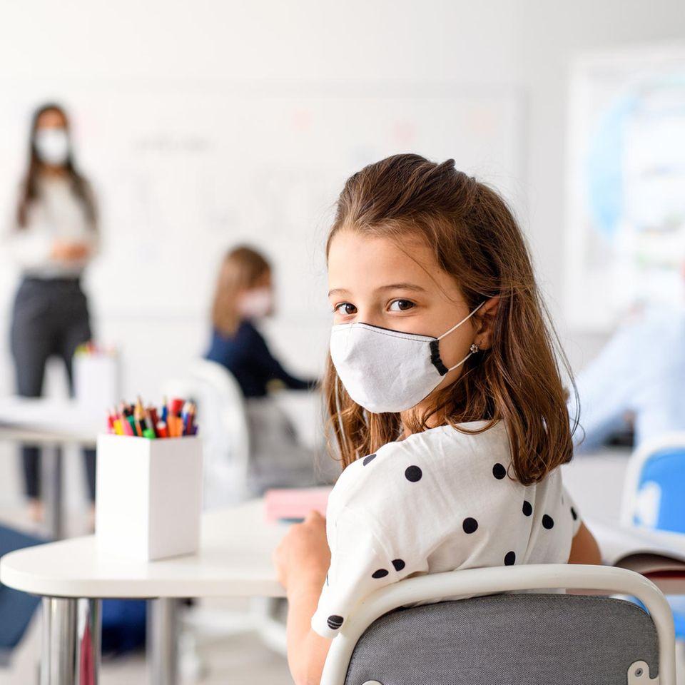 Corona aktuell: Schulkind mit Maske im Klassenzimmer