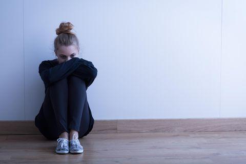 Psychologie: Eine junge Frau sitzt vor einer weißen Wand