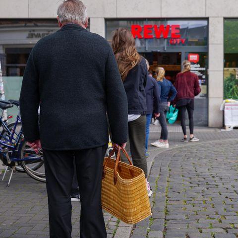 Corona aktuell: Eine Schlange vor einem Supermarkt