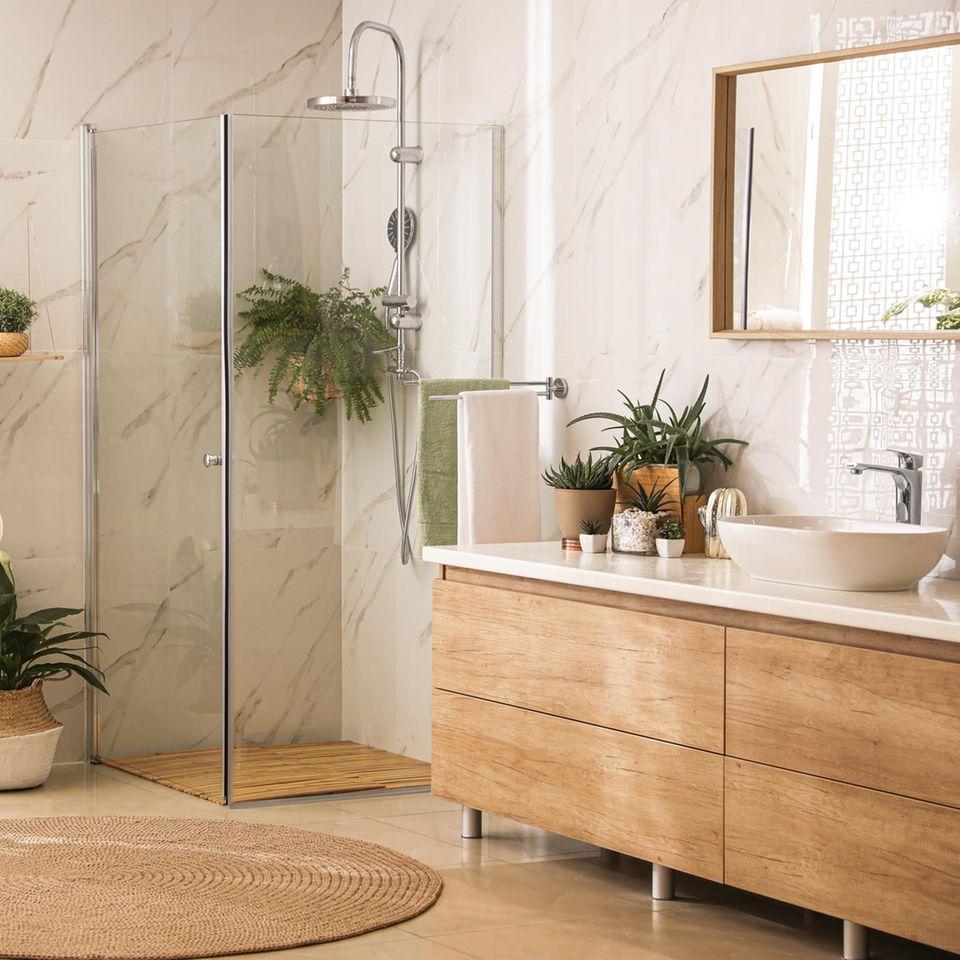 Bad einrichten: helle Badezimmer-Einrichtung, Pflanzen, Kommode, Duschkabine