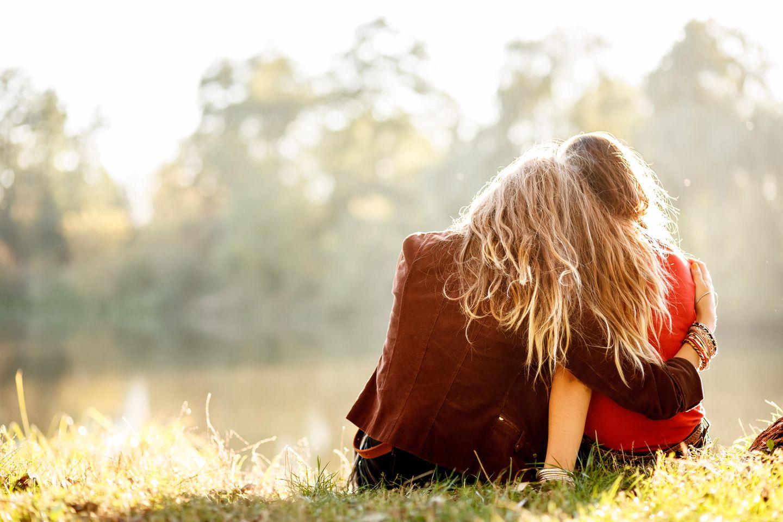 Psychologie: Zwei emotional verwandte Frauen sitzen an einem See