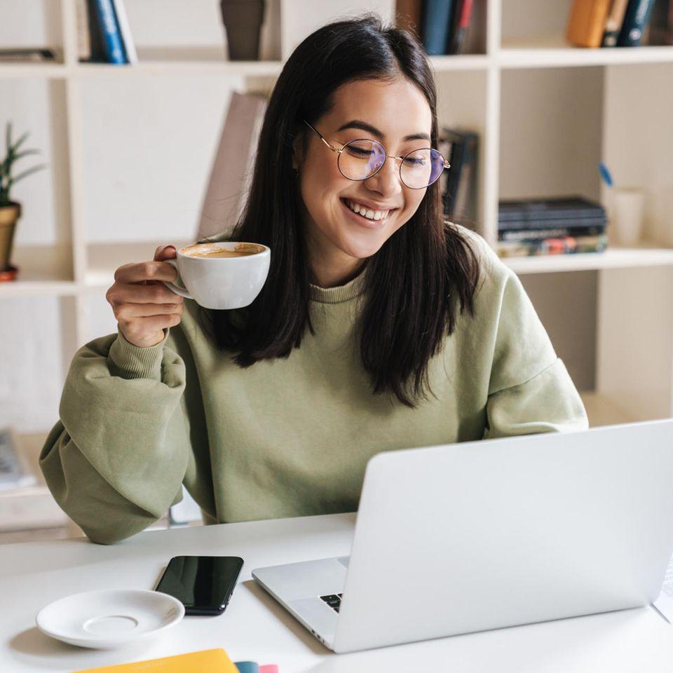 Feynman-Methode: Frau sitzt am Schreibtisch, hält eine Kaffeetasse in der Hand und blickt auf den Laptop.