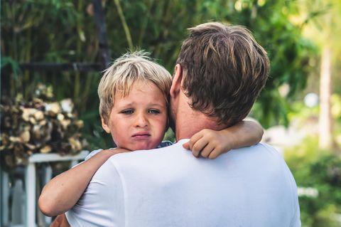 Dinge, die toxische Eltern tun: Trauriges Kind auf dem Arm vom Papa