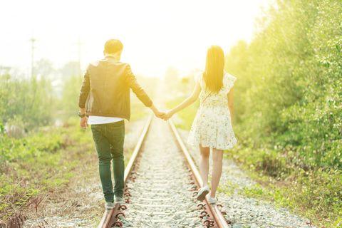 Psychologie: Ein Paar spaziert Hand in Hand über Bahnschienen