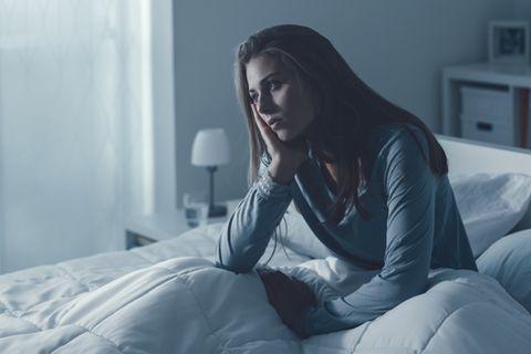 Schlafmangel: Frau sitzt im Bett