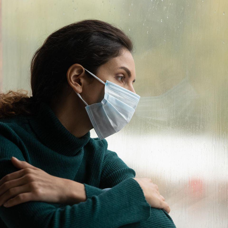 Corona: Frau mit Maske alleine am Fenster