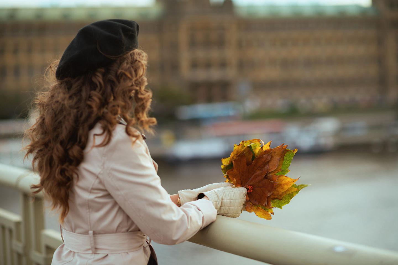 Coronakrise: Eine Frau mit Hebstlaub auf einer Brücke