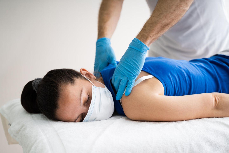 Corona-Ausbruch: Frau mit Mundschutz bei der Physiotherapie