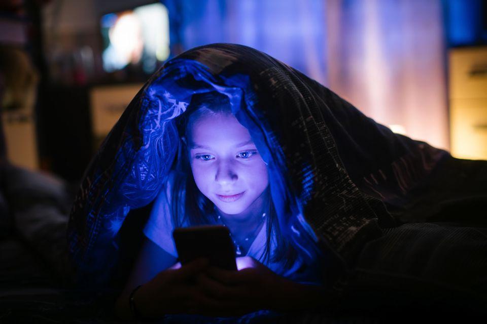 Smartphones: Mädchen im Bett mit Handy