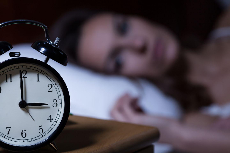 Wochentag: Schlaflose Frau mit Wecker