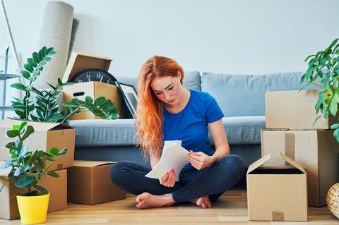 BRIGITTE-Studie: Frau sitzt mit Unterlagen zwischen Kartons