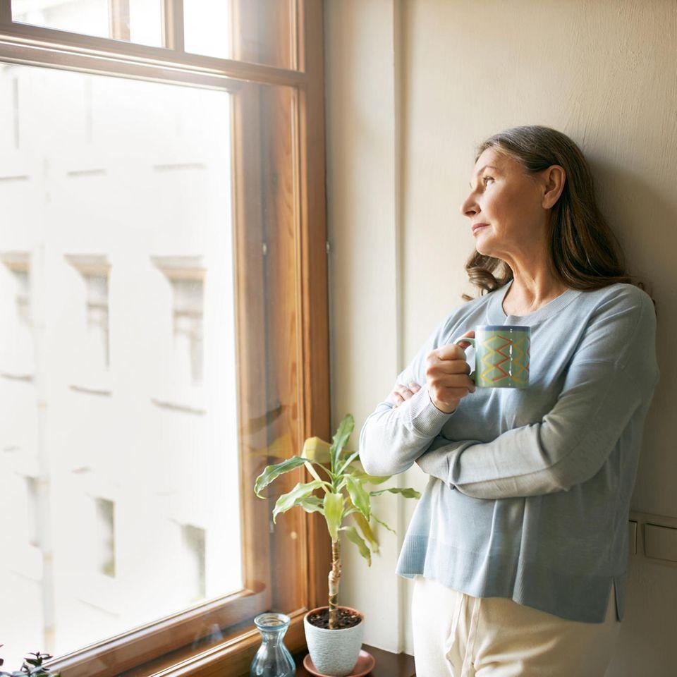 BRIGITTE-Studie: ältere Frau lehnt am Fenster