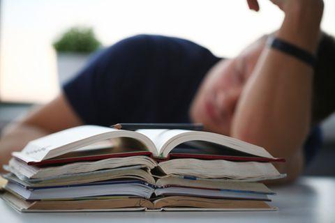 Schlau träumen: schlafender Mann vor Büchern