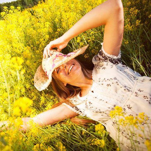 Positives Mindset: Frau liegt auf einer Sommerwiese
