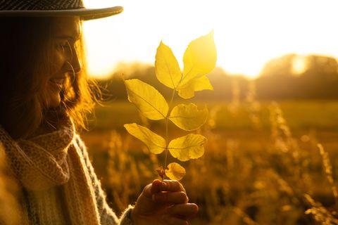 Horoskop: Eine junge fröhliche Frau mit Blättern in der Hand