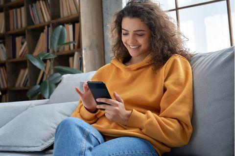 Tinder anschreiben: Frau hält Smartphone in der Hand und lächelt