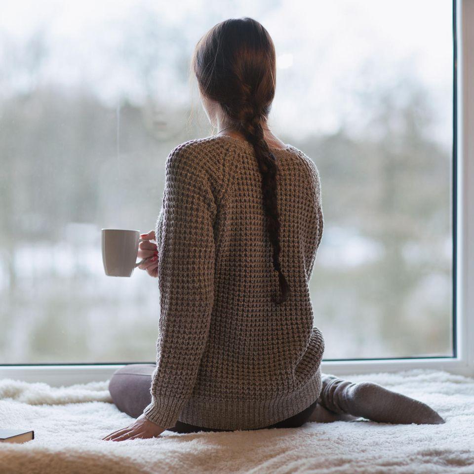 Psychologie: Eine nachdenkliche Frau schaut aus dem Fenster