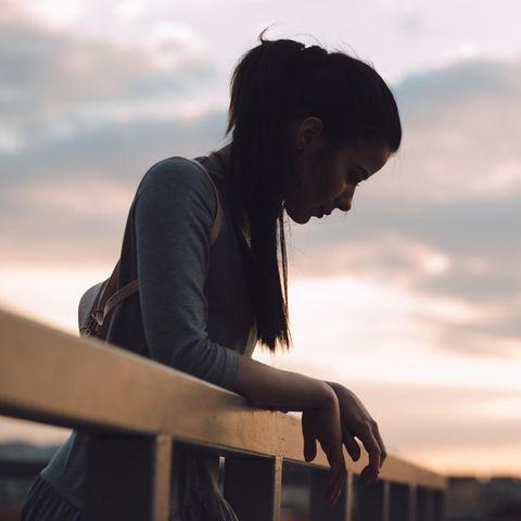 Horoskop: Eine verunsicherte Frau auf einer Brücke