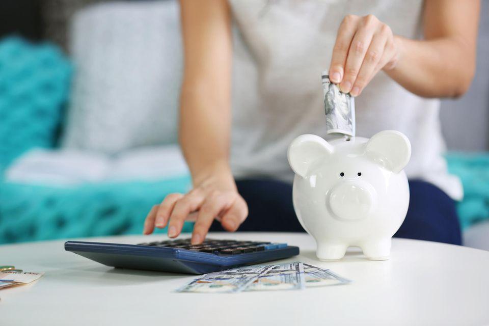 3 Dinge, die wohlhabende Menschen tun, um ihr Geld zu vermehren: Hand steckt Geld ins Sparschwein