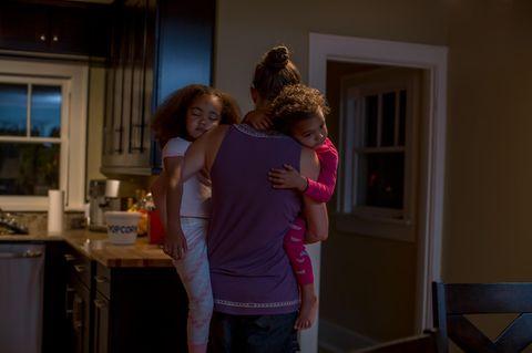 Frau trägt ihre Kinder auf dem Arm