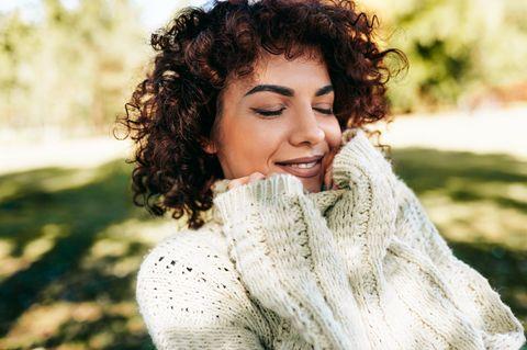 Horoskop: Eine fröhliche Frau in Strickpulli