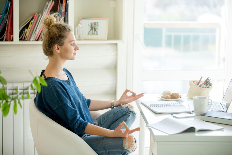 Achtsamkeitstraining: Frau sitzt am Schreibtisch und meditiert
