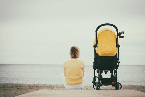 Kind alleine lassen: Mutter mit Kinderwagen am Strand
