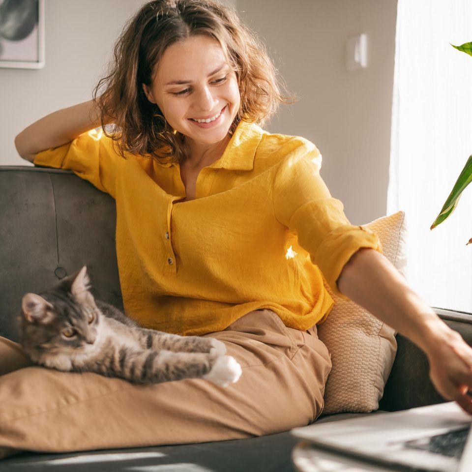 Selbstfürsorge: Frau mit Katze auf dem Sofa