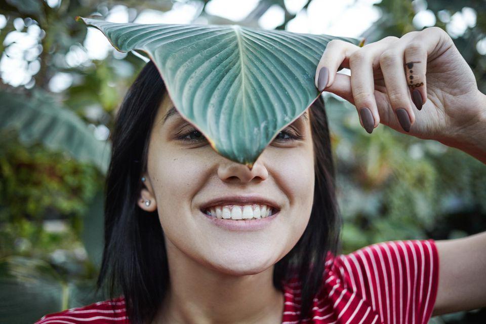 Green Beauty: Lächelnde Frau steht zwischen Pflanzen