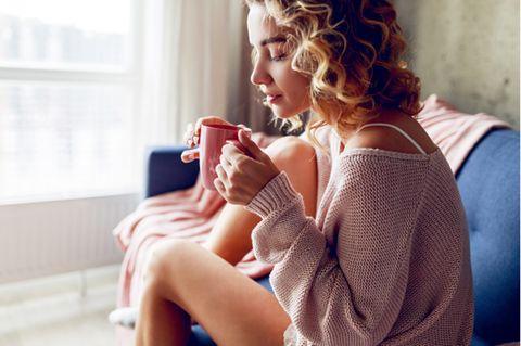 Minderwertigkeitskomplexe: Frau trinkt Tee und sitzt auf der Couch