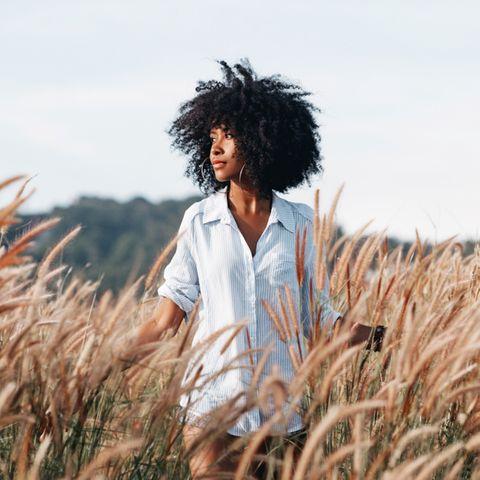 Selbstfürsorge: Frau geht durch ein Weizenfeld.