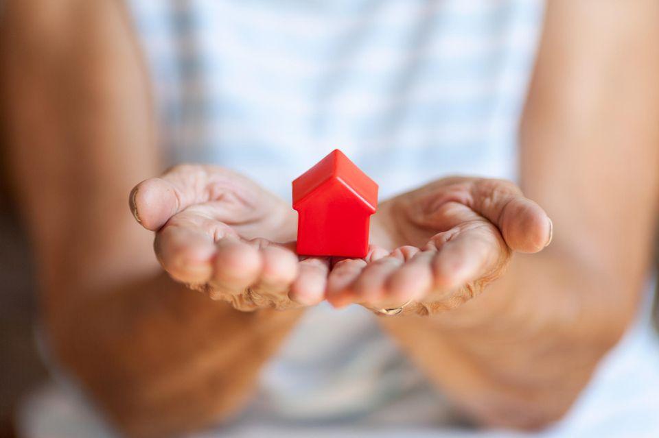 Erbe schützen: Dame mit kleinem Haussymbol in der Hand