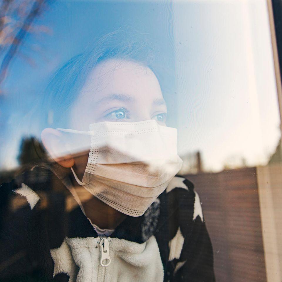 Kind mit Maske schaut aus dem Fenster