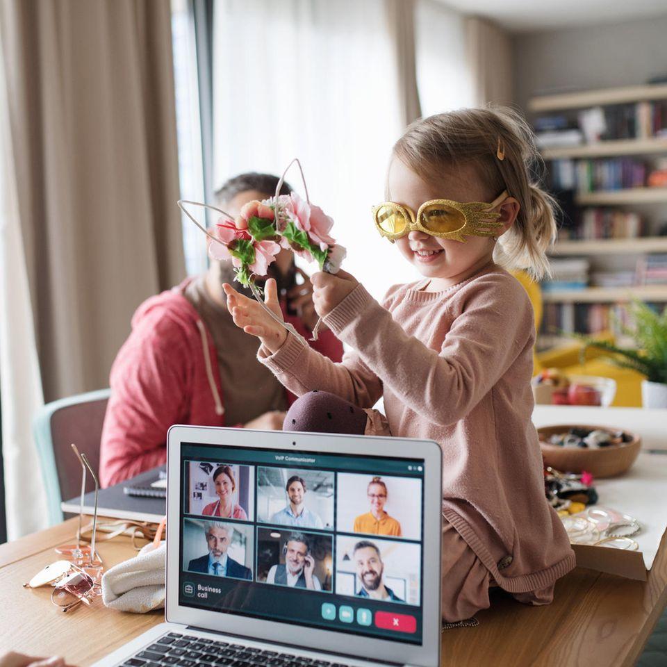 Kind sitzt auf Tisch und spielt während Eltern arbeiten