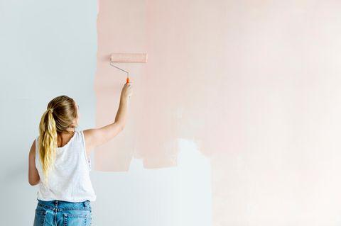 Wohnzimmer streichen: Mit diesen Tipps gelingt es, junge Frau, rosa Wand