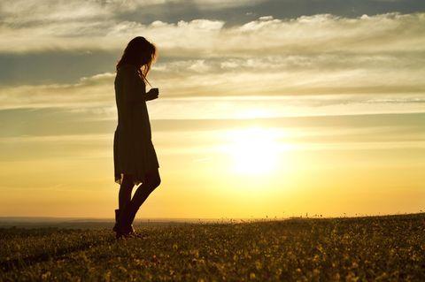 Horoskop: Eine unsichere Frau vor einem Sonnenuntergang