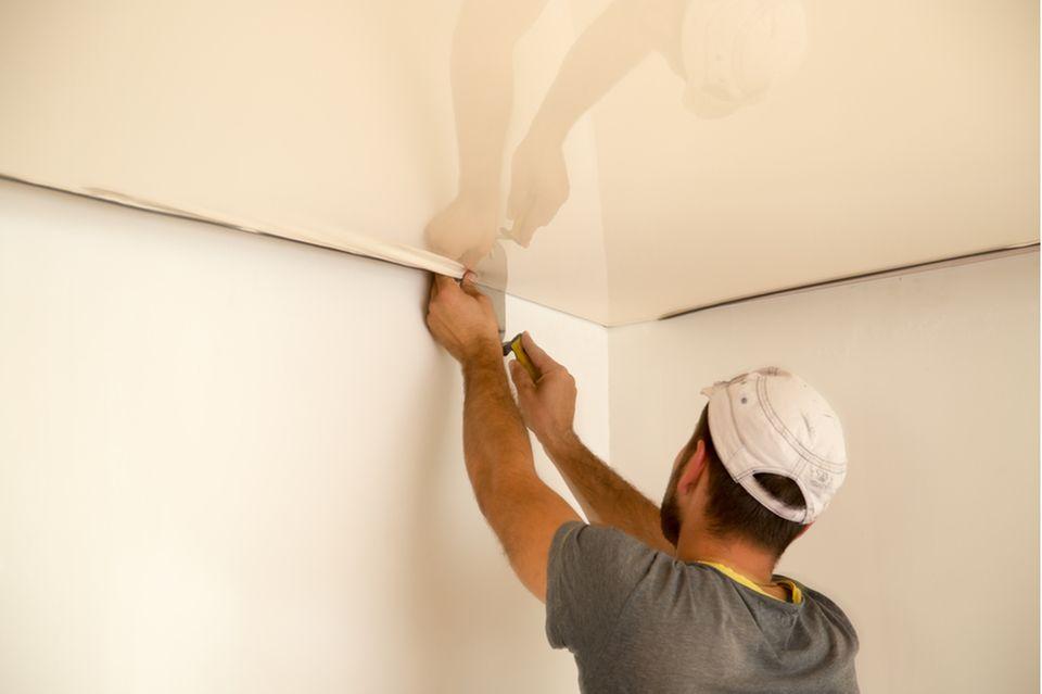 Küche renovieren: Monteur installiert Spanndecke