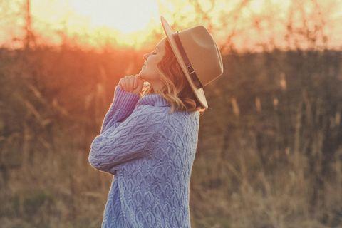 Horoskop: Eine Frau in Pullover schaut in den Himmel