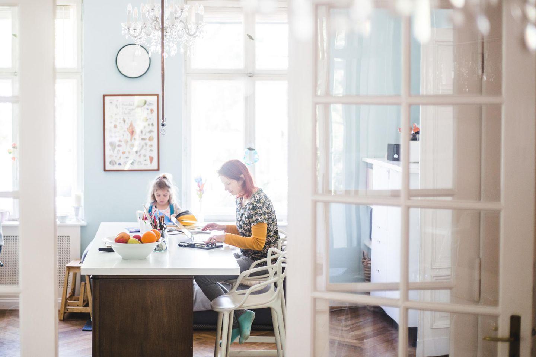 Mutter sitzt mit Tochter am Küchentisch