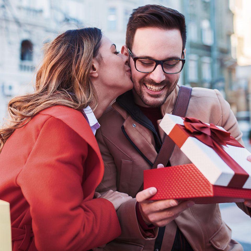 Geschenke für den Partner: Mann wird von Frau beschenkt