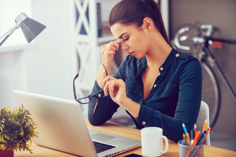 Überforderung: Frau sitzt am Schreibtisch und fasst sich an den Kopf.