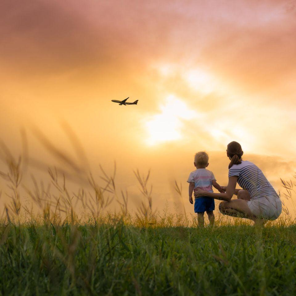 Martina von Münchhausen: Frau und Kleinkind auf Wiese beobachten Flugzeug