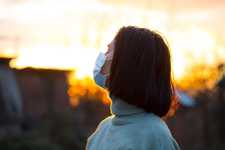 Corona aktuell: Frau mit Maske im Sonnenaufgang