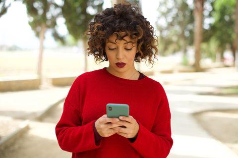 Lovebombing: Frau in rotem Pullover am Telefon