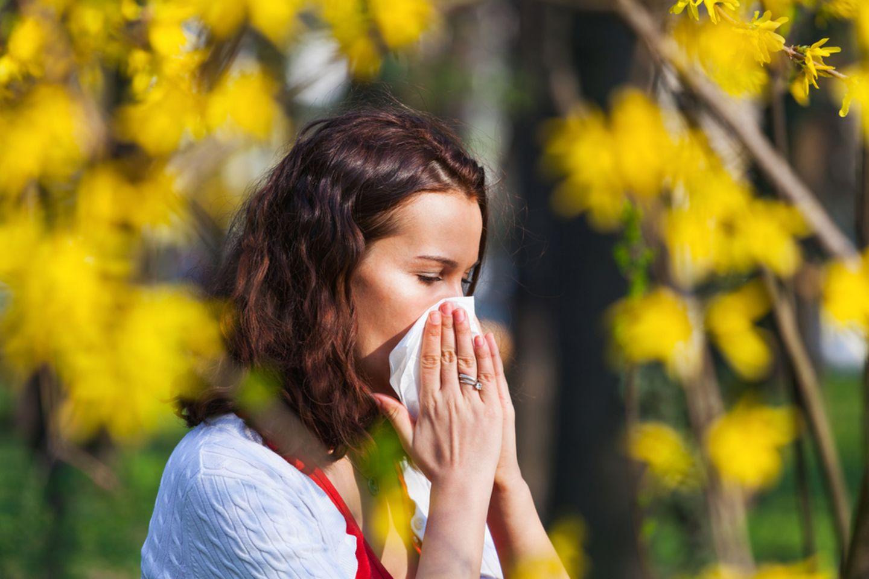 Corona aktuell: Frau putzt sich die Nase
