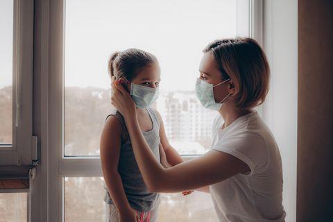 Corona aktuell: Mutter setzt Kind Maske auf