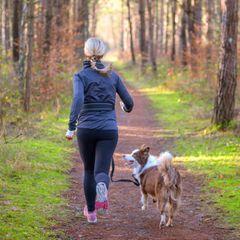 Eine Frau joggt mit ihrem Hund durch den Wald