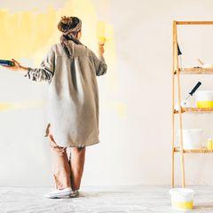 Eine Frau streicht ihre Wand